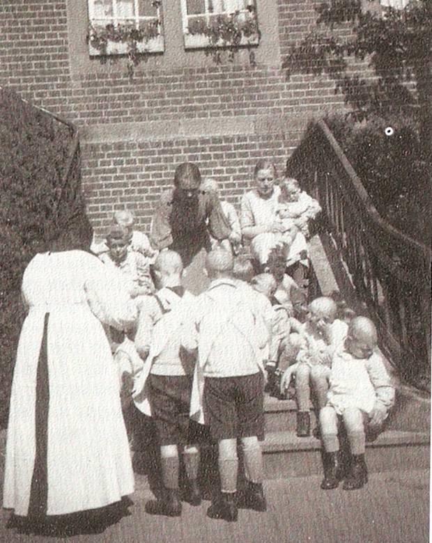 """Behinderte Kinder mit den betreuenden Ordensschwestern vor dem """"Schutzengelhaus"""" von Haus Hall"""